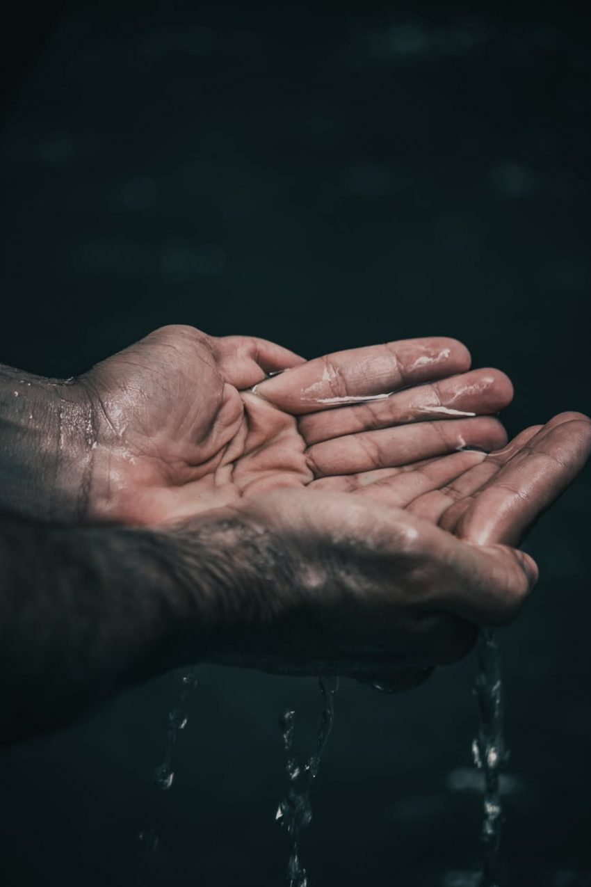 person holding water in cupped hands