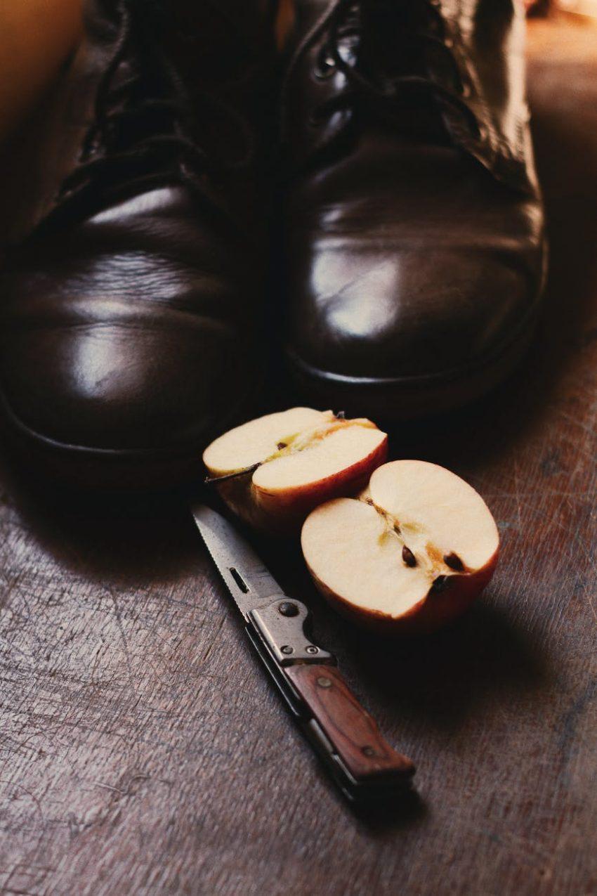 sliced apple fruit near black boots
